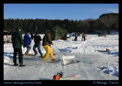 Pulling out part of the ice for the hole - for Ice Diving... by Margo Cavis 